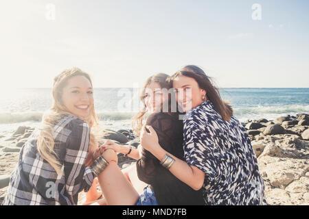 Groupe de belle femme jeune et souriant parlant autour d'une plage de galets de Tenerife. équipe filles de s'amuser ensemble