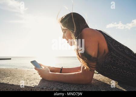 De beaux cheveux longs femme espagnole utilisation téléphone mobile pour envoyer des messages pendant les vacances à Tenerife. Fixer sur un mur près de la plage sous un ciel bleu w Banque D'Images