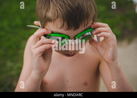 Un garçon portant des lunettes de natation vert sur une journée ensoleillée Banque D'Images