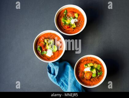Soupe froide gaspacho de tomates heirloom surmontée avec de l'avocat, les tomates cerises, la coriandre et une dallop de crème sure Banque D'Images