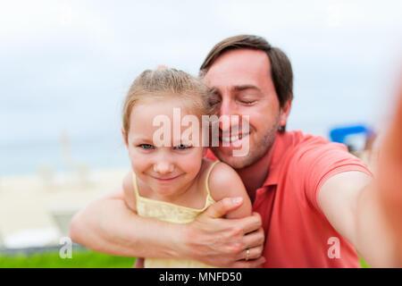 Père de famille heureuse et son adorable petite fille à plage tout en selfies Banque D'Images