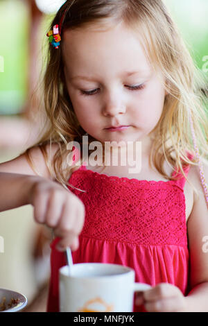 Adorable petite fille dans le boire du chocolat chaud Banque D'Images
