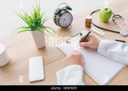Femme médecin à écrire des notes, les antécédents médicaux du patient ou la médecine prescription sur presse-papiers papier pendant l'examen médical à l'hôpital office Banque D'Images