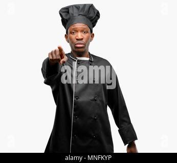 Jeune chef cuisinier noir wearing hat dirigée vers l'avant avec le doigt