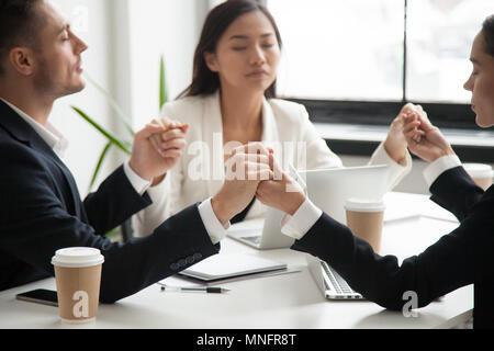 L'équipe de l'entreprise tenant les mains en priant pour le succès Banque D'Images