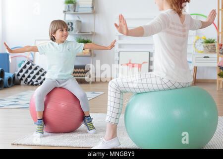 Physiothérapeute et jeune garçon faisant exercice s'étendant sur les boules colorées dans cette chambre lumineuse Banque D'Images
