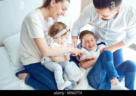 Famille heureuse de jouer couché sur le lit dans la chambre à coucher. Banque D'Images