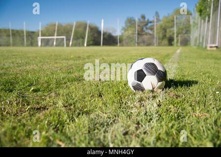 Le football, c'est allongé dans l'herbe sur un terrain de football. Il se trouve sur la ligne extérieure. Dans l'arrière-plan vous pouvez voir le but de football. Il s'agit d'un soleil Banque D'Images