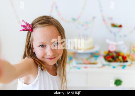 Adorable petite fille princesse avec couronne à kids Birthday party prendre selfies Banque D'Images