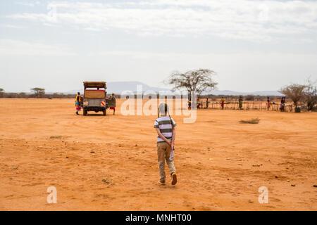 Adorable petite fille en Kenya safari à pied vers véhicule ouvert Banque D'Images