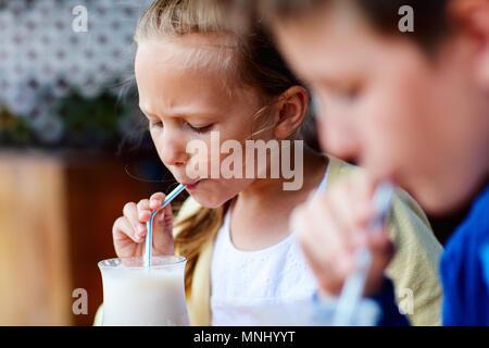 Les jeunes frère et sœur de lait frappé au café en plein air potable Banque D'Images