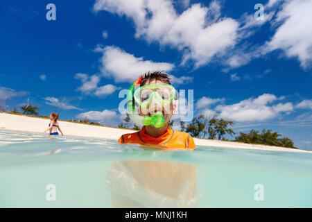 Happy boy avec masque et tuba dans l'eau turquoise de l'océan tropical Banque D'Images