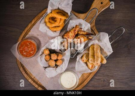 Snack pour la bière sous forme de fromage nuggets de poulet frit et anneaux de jambes Banque D'Images
