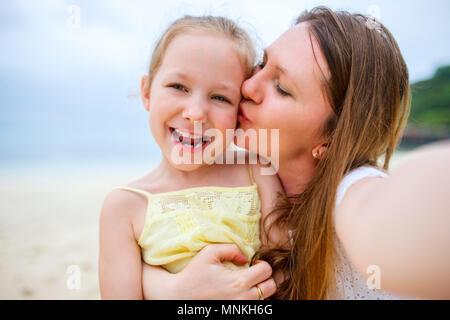 Famille heureuse mère et son adorable petite fille à la plage faire selfies