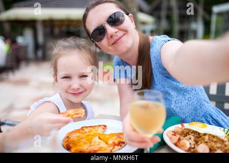 Heureuse mère et son adorable petite fille à l'extérieur restaurant prenant tout en ayant selfies délicieux déjeuner Banque D'Images