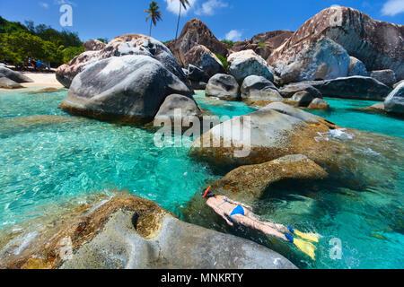 Jeune femme plongée dans l'eau tropicale turquoise entre d'énormes rochers de granit aux bains beach area, British Virgin Islands, Caribbean Banque D'Images