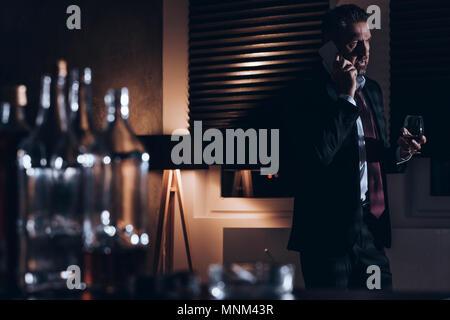 A souligné l'homme d'âge moyen d'un costume à parler au téléphone et la tenue d'un verre d'alcool tout en se tenant dans une pièce sombre avec des bouteilles d'alcool vides dans un lecteur blu Banque D'Images