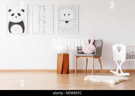 Lumière sur le tabouret en bois à côté de gray fauteuil avec coussin, lit bébé blanc et tapis chambre d'enfant avec galerie