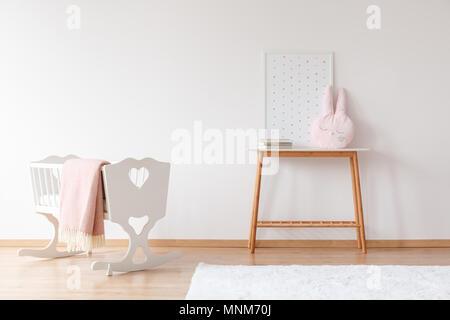 Lit bébé blanc avec couverture rose près de table en bois avec un oreiller dans la chambre de bébé et de l'affiche avec copie espace