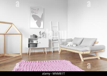 Big soft rose tapis sur le plancher en bois dans cette chambre lumineuse avec un canapé