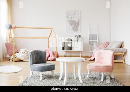 Gris et Rose petit mignon debout sur des chaises confortables tapis moelleux en chambre de bébé