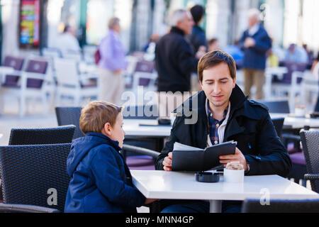 Jeune père et son fils au café en plein air sur la journée d'automne