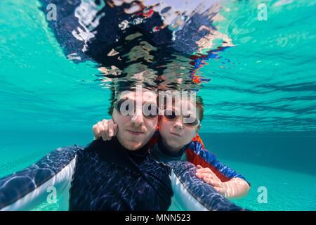 Père et fils nager sous l'eau et faire selfies Banque D'Images