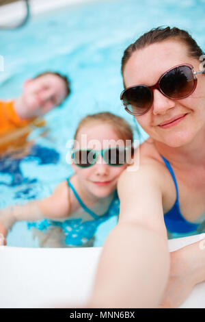 Mère de famille heureuse et ses enfants à l'extérieur piscine en tenant sur selfies vacances tropicales Banque D'Images