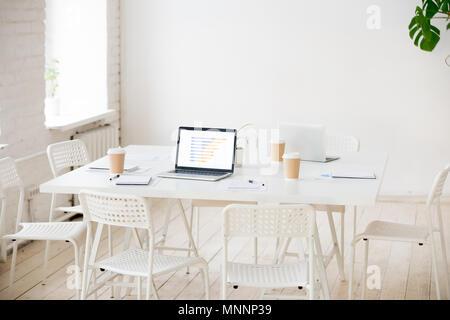 Table de réunion avec les ordinateurs portables et de café dans la chambre bureau vide Banque D'Images