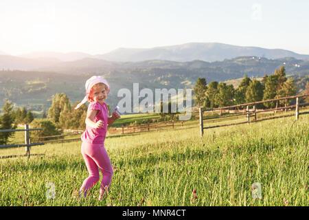 Cute little baby girl jouer dehors tôt le matin dans la pelouse et admirer les montagnes. Copie de l'espace pour votre texte Banque D'Images