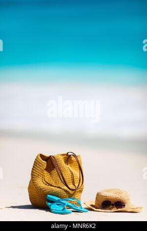 Sac de paille, lunettes de soleil, serviette et tongs sur une plage tropicale Banque D'Images