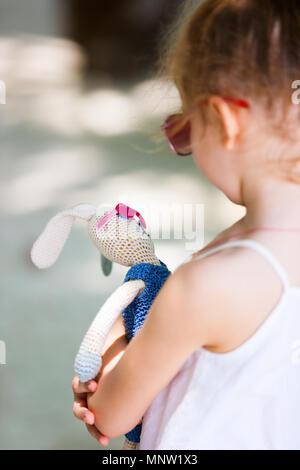 Petite fille avec son jouet favori lapin tricoté les deux portant des lunettes roses à l'extérieur sur journée d'été Banque D'Images