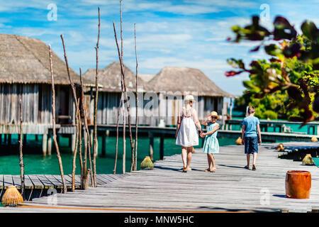 Vue arrière de l'heureuse famille belle balade sur la jetée en bois pendant les vacances d'été à luxury resort Banque D'Images