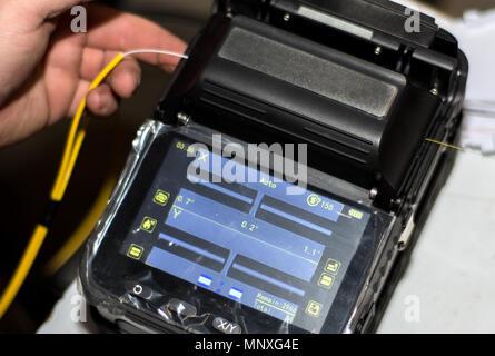 Câble fibre optique de raccord avec la fusion de fibre optique instrument d'épisseur outil professionnel. Internet moderne et rapide et le réseau concept Banque D'Images