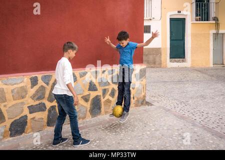 Garçons jouant avec un ballon de football à l'extérieur dans la rue