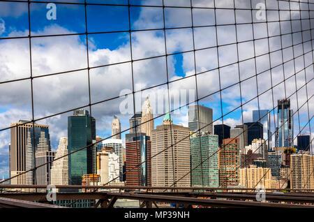L'horizon de Manhattan comme vu à travers les mailles du pont de Brooklyn à New York City, USA.