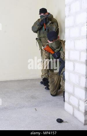 Mercenaire avec AK-47 jeter une grenade à l'intérieur du bâtiment Banque D'Images