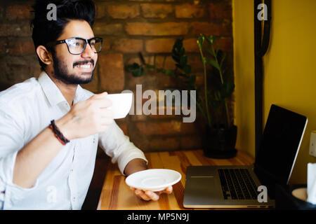 Young Asian Indian businessman using computer pendant les pause au café, vous détendre avec une tasse de café. Banque D'Images