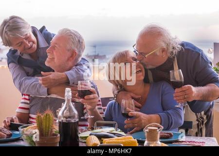 Deux mature couple rester ensemble avec amour sourires et baisers lors d'un dîner en plein air, sur la terrasse sur le toit avec vue sur les toits et de l'océan. la joie et avoir f Banque D'Images