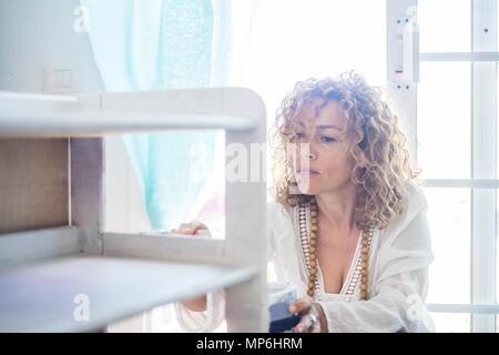 Belle caucasian woman diy faire elle-même vous-même d'un mobilier renouvelé à la maison avec la lumière de la fenêtre. expression concentrée pour l'âge moyen dame pa Banque D'Images