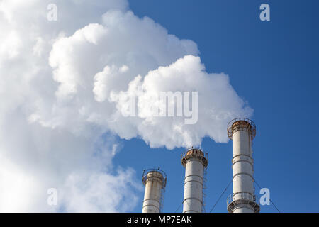 Fumeurs tuyaux nuages contre fond de ciel bleu. La contamination de l'air dioxyde de carbone. La pollution de l'environnement Banque D'Images