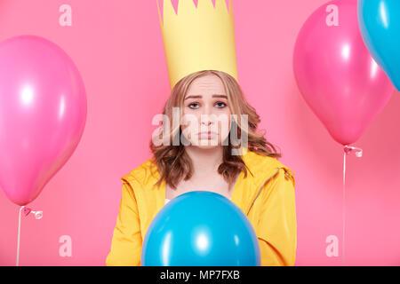 Jeune femme déçue dans party hat entouré de ballons colorés, isolé sur fond rose pastel. Triste Anniversaire concept.