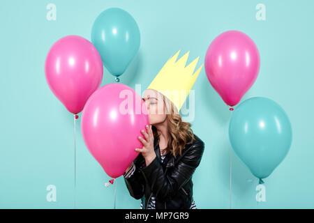 Magnifique jeune femme en blouson de cuir et party hat kissing balloon colorés, isolé sur fond de couleur bleu pastel. Concept d'anniversaire.