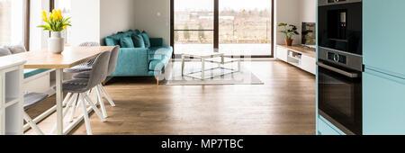 Tulipes jaunes sur table en bois à l'intérieur d'appartements moderne avec canapé bleu. Photo réelle Banque D'Images