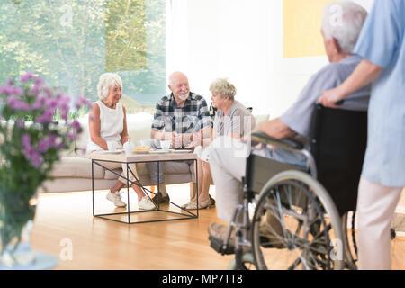 Groupe de personnes âgées des gens assis sur le canapé à l'heure du déjeuner dans la salle commune Banque D'Images