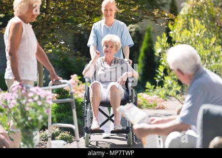 Smiling senior femme dans un fauteuil roulant de passer du temps avec son infirmière sur la terrasse sur une journée ensoleillée Banque D'Images