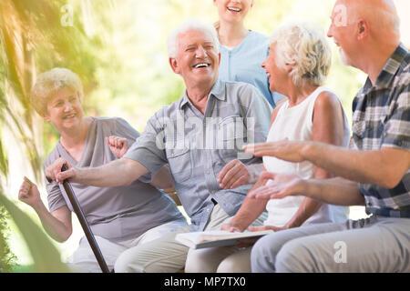 Group of smiling senior friends passer du temps ensemble assis dans le parc Banque D'Images