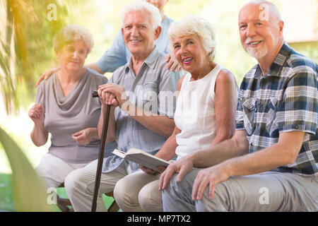 Smiling personnes âgées de passer du temps ensemble à la maison de soins infirmiers de patio Banque D'Images