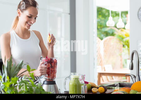 Smiling woman squeezing jus d'orange dans blender avec des tranches de melon et de la betterave pendant la préparation en cuisine smoothie Banque D'Images
