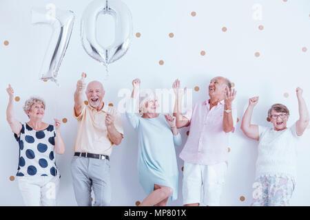 Les aînés positifs célébrant l'anniversaire de grand-père de famille avec des ballons d'argent Banque D'Images
